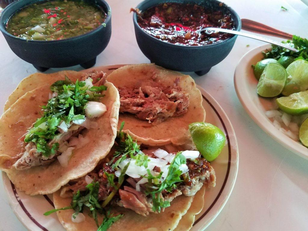 Barbacoa Lamb on tacos with salsas, onions and cilantro.