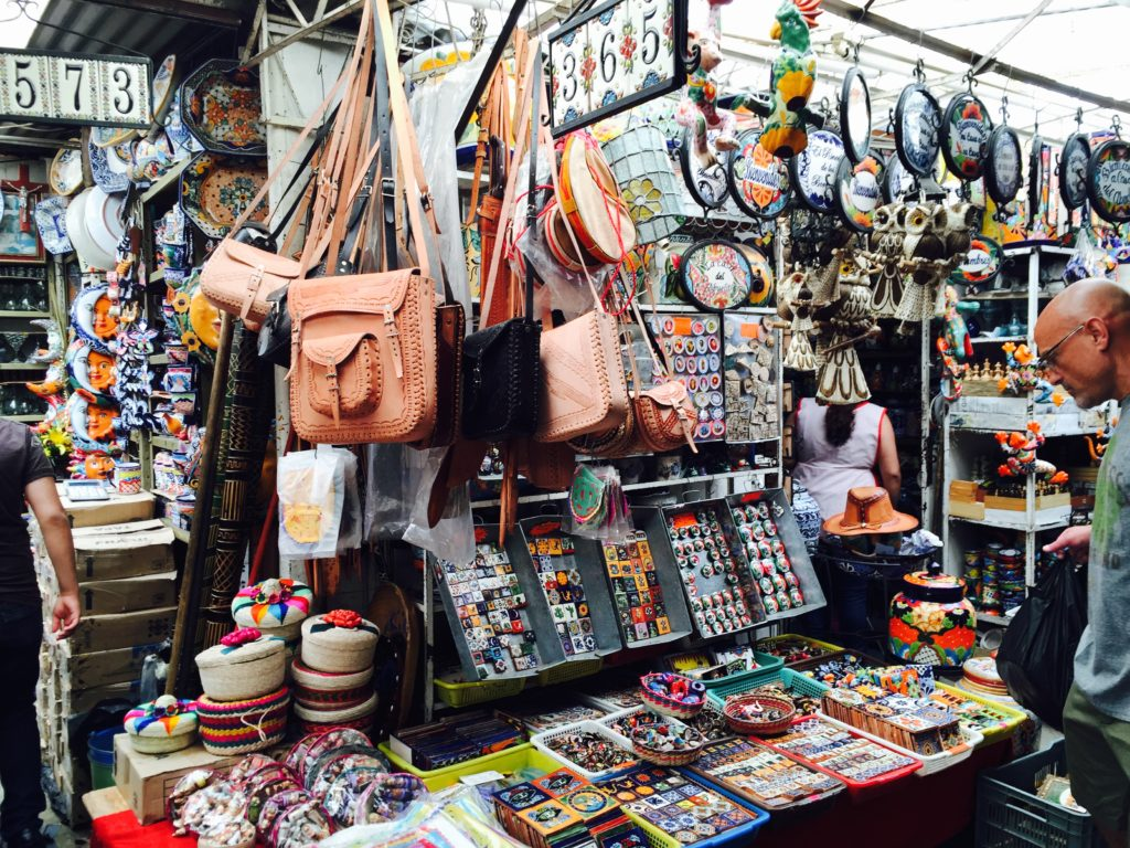 Leather goods, handmade tortilla warmers and decorative tiles at La Cuidadela Artisan Market