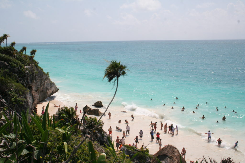 People enjoying the blue water and white sandy beach at Tulum, Mexico