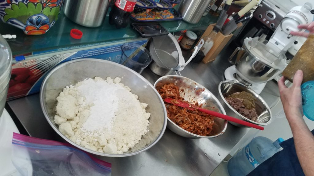 Bowls of masa, pork and tongue ready for tamales